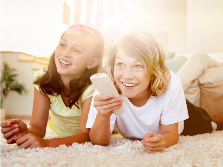 Kinder im Wohnzimmer mit Fernbedienung